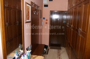 Много тесен коридор в който са събрани шесткрилен гардероб,шкаф за обувки ,шкаф за сядане и пано за връхни дрехи